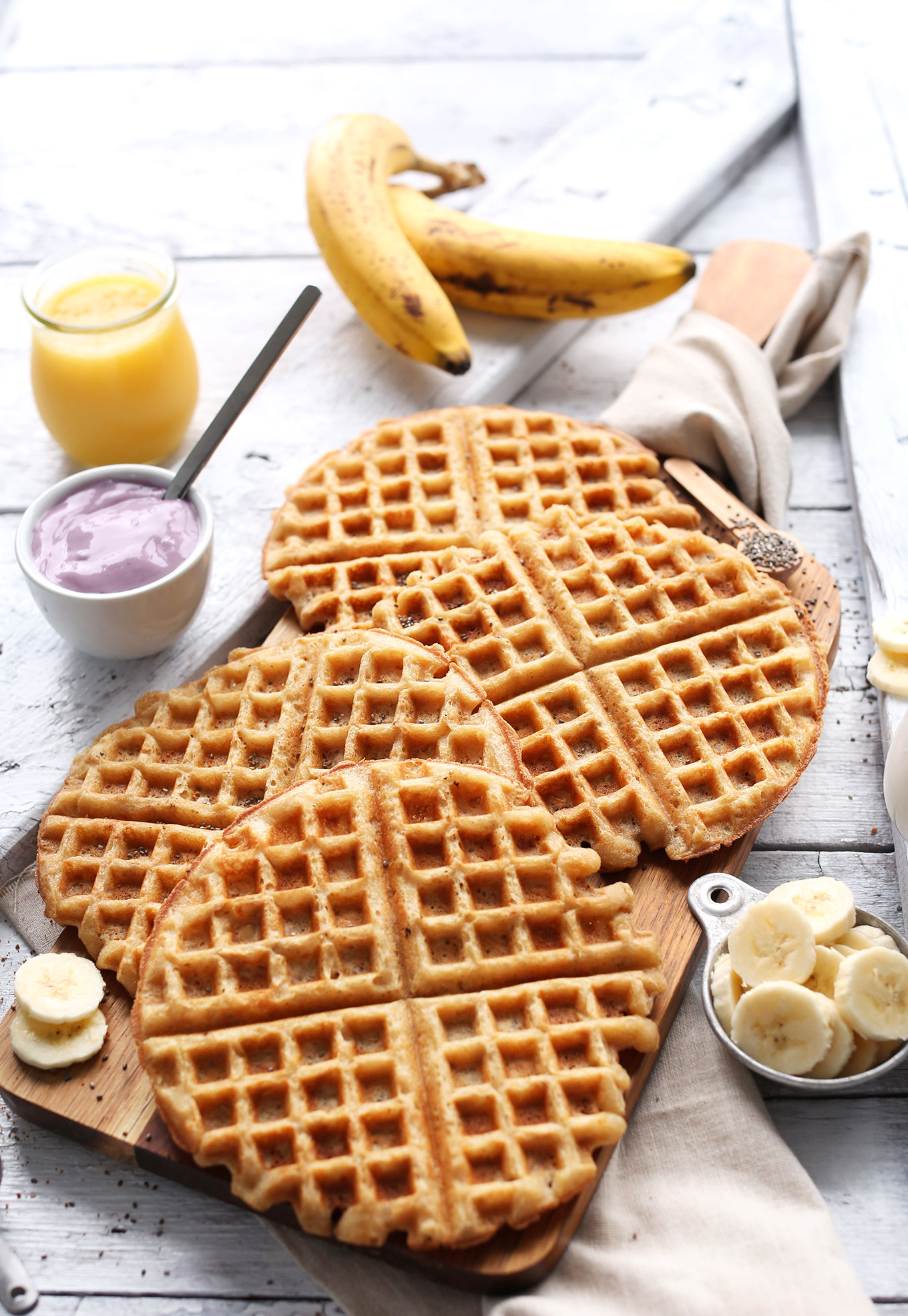 Homemade Yogurt Waffles alongside fresh bananas, yogurt, and orange juice