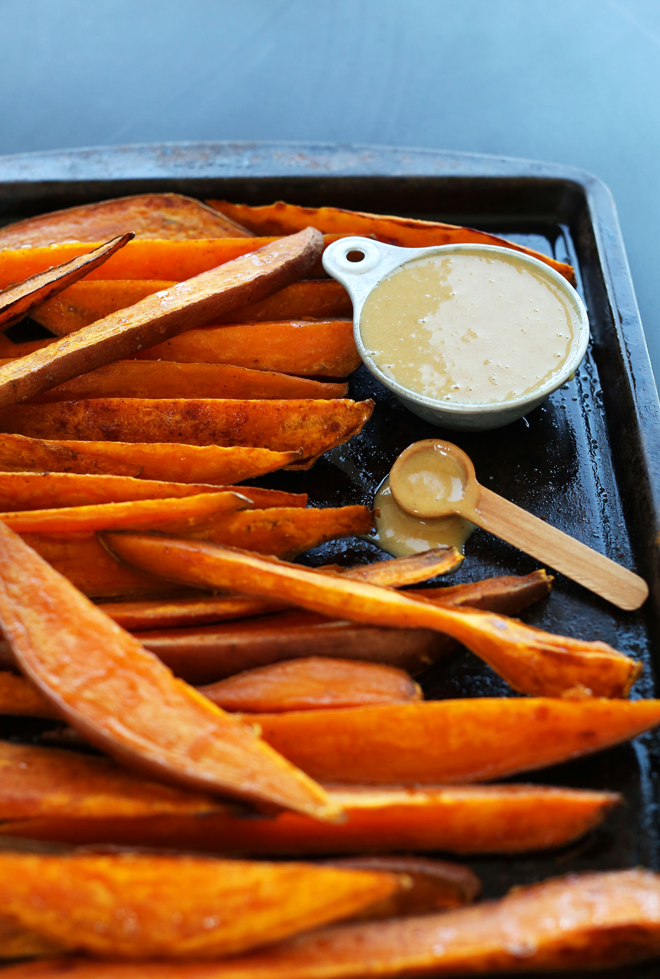 Baking sheet with baked sweet potatoes and delicious vegan No-Honey Mustard Dipping Sauce