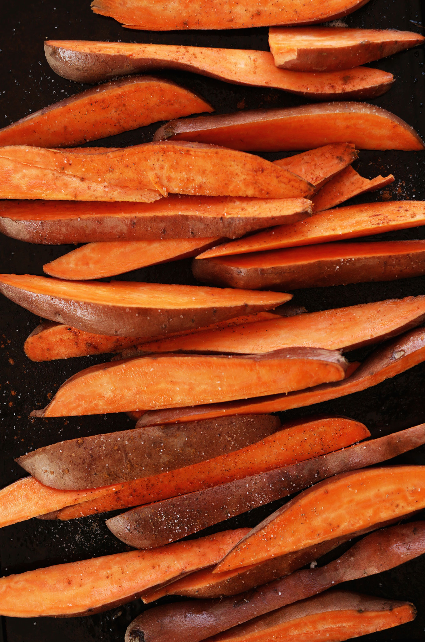 Baking sheet with Sweet Potato Wedges topped with salt and spices