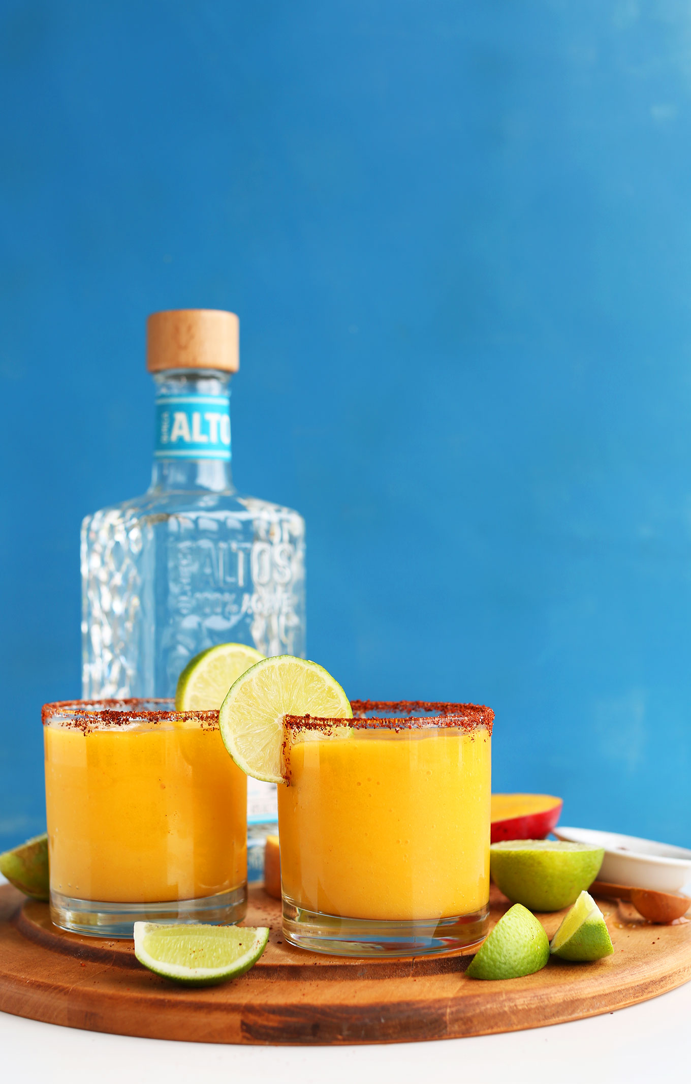 Cutting board with Spicy Sweet Mango Chili Lime Margaritas and ingredients used to make them