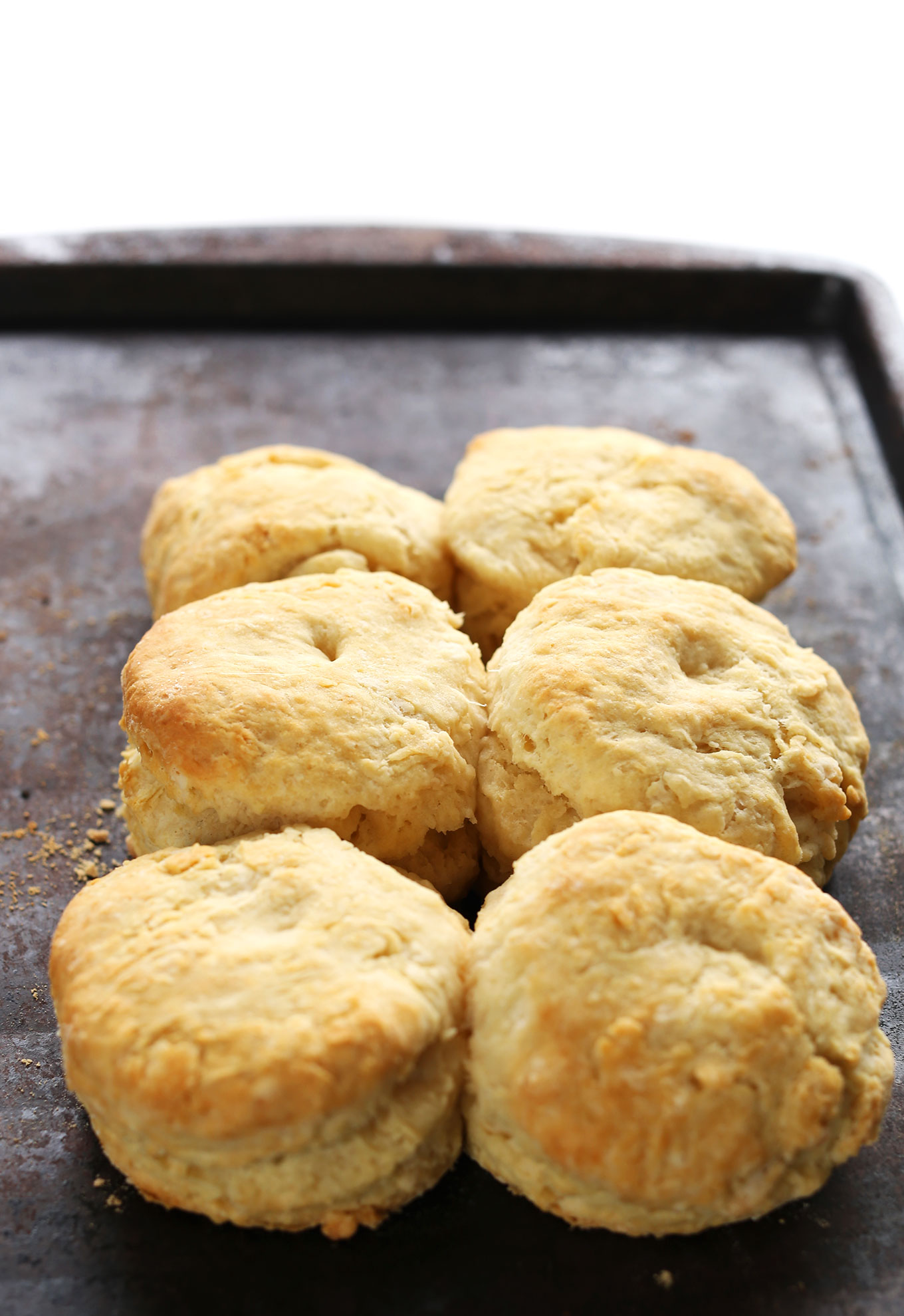 Baking sheet with six freshly baked flaky vegan biscuits