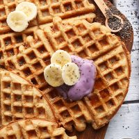 Cutting board with Coconut Yogurt Waffles topped with sliced banana and yogurt