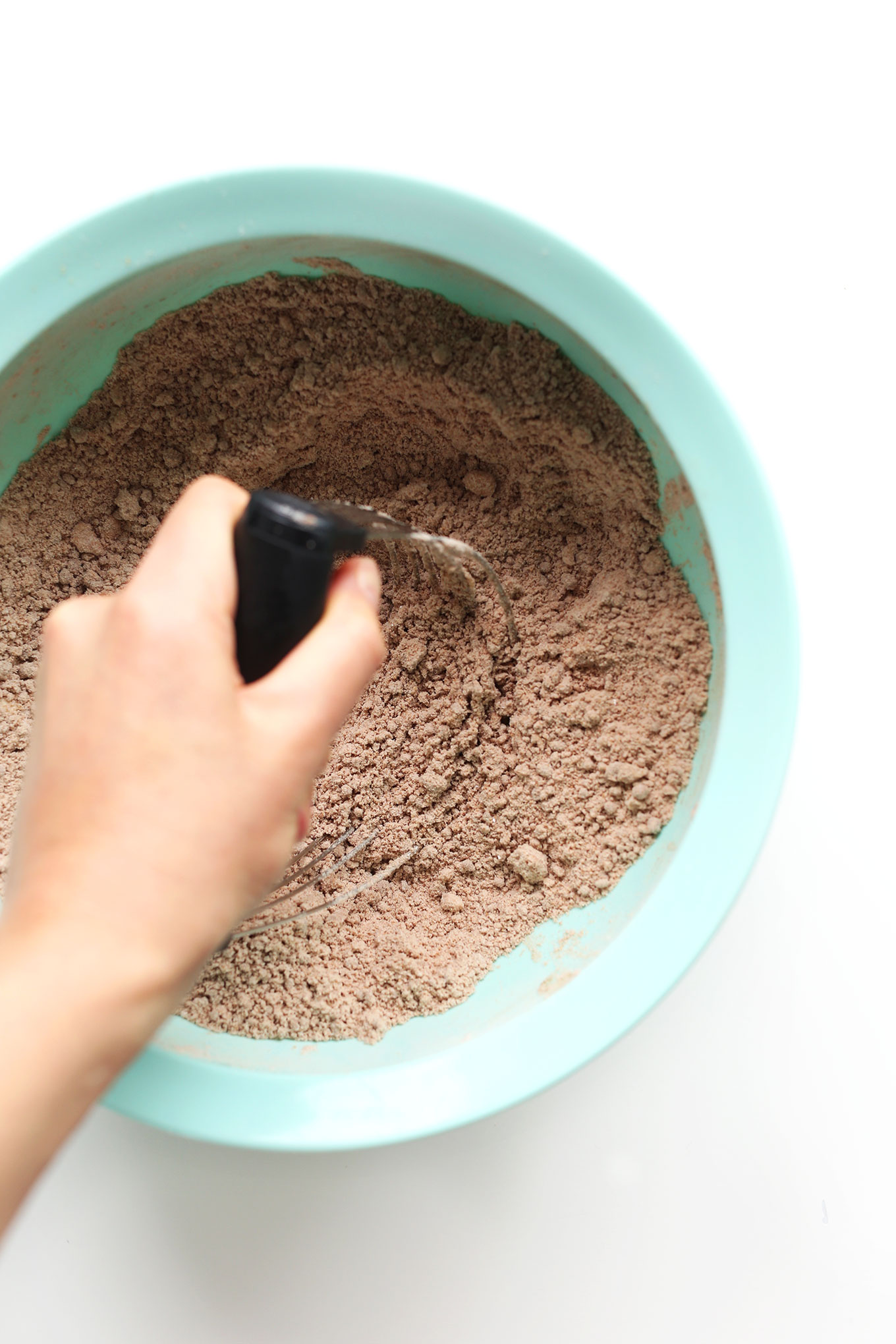 Using a pastry cutter to cut coconut oil into dry ingredients
