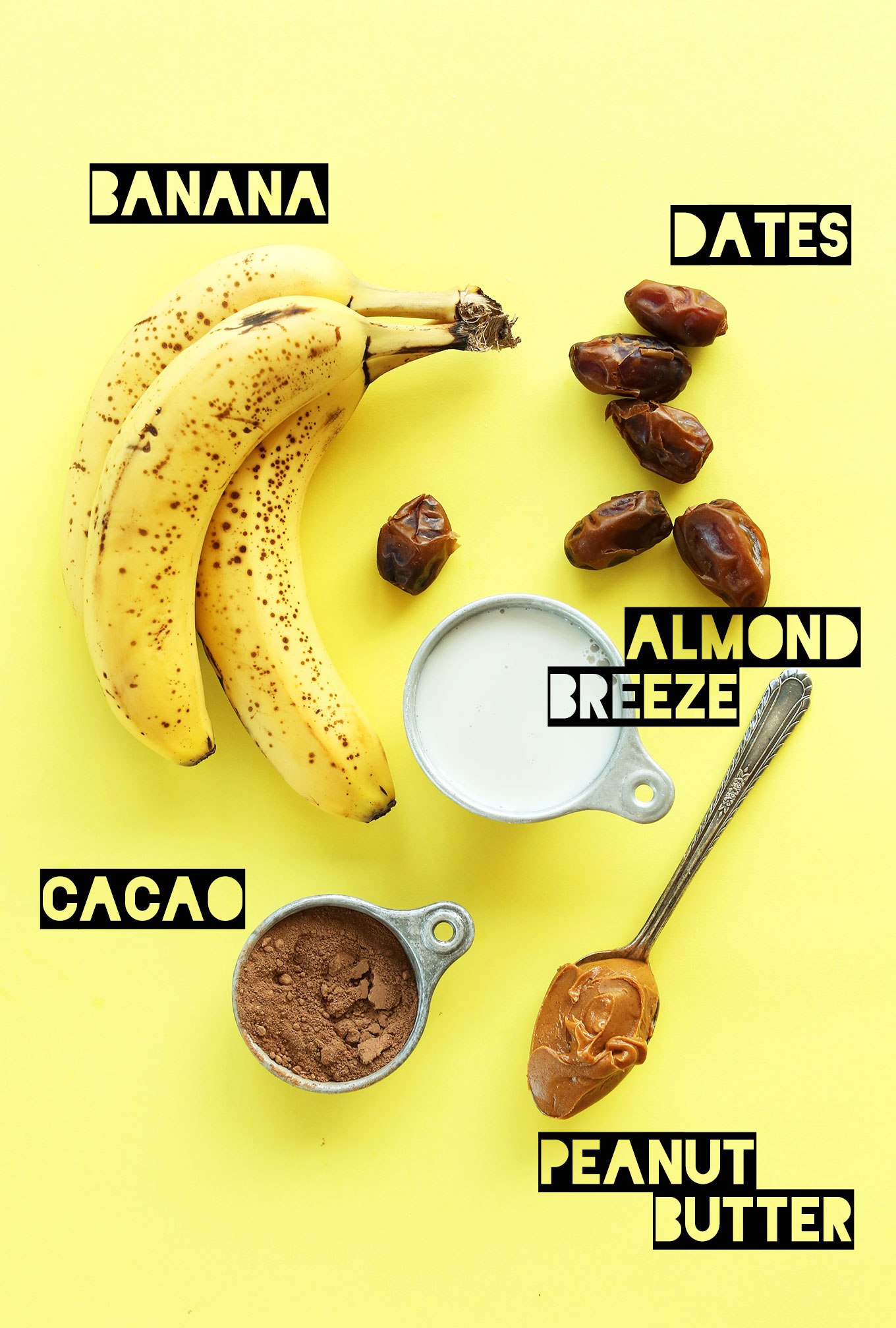 Bananas, dates, almond milk, cacao powder, and peanut butter for making a homemade vegan milkshake