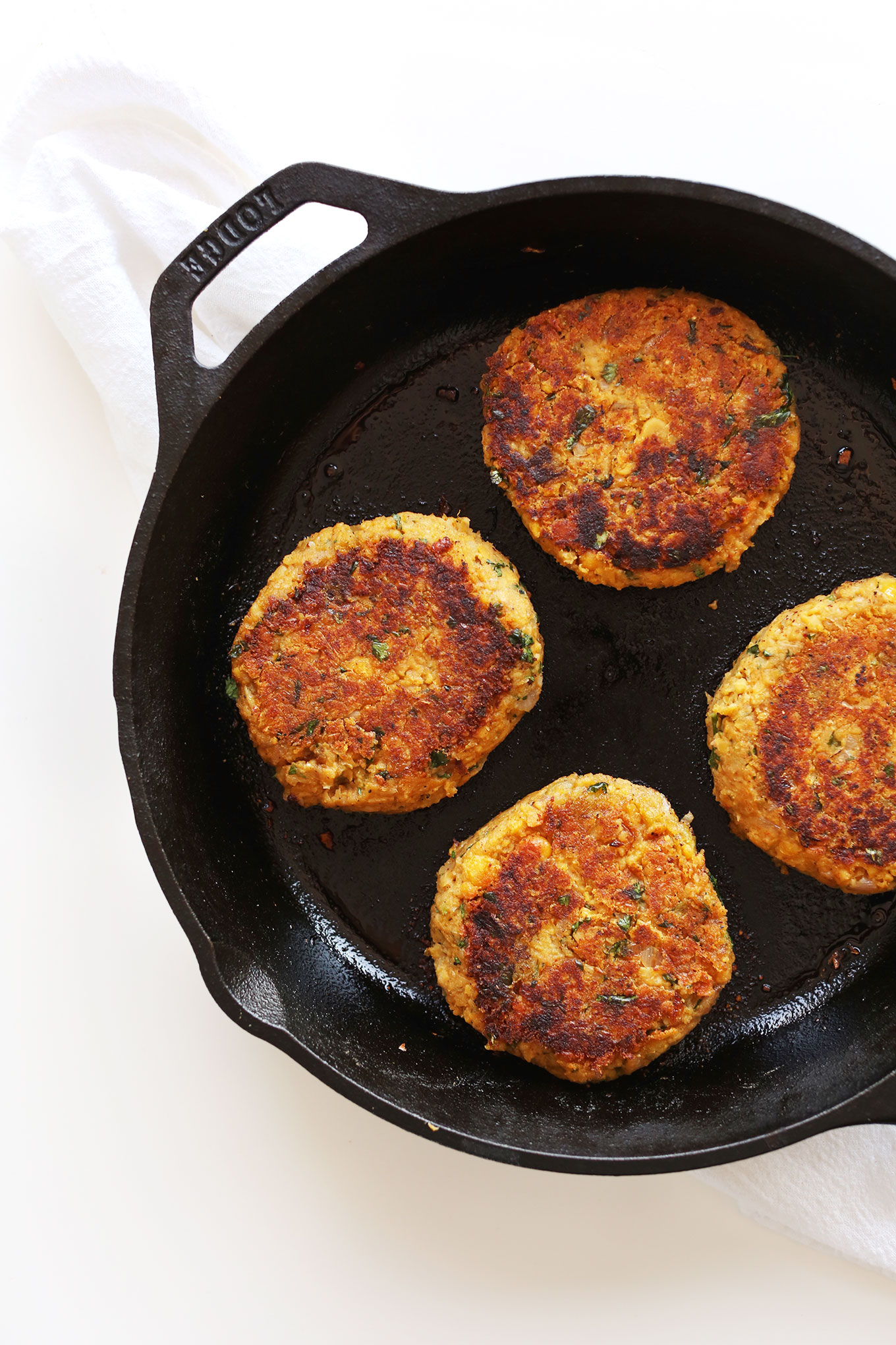 Cast-iron skillet filled with perfectly browned Green Chili Veggie Burgers for a vegan dinner