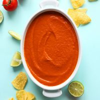White ceramic dish filled with homemade Blended Red Salsa beside tortilla chips, limes, and tomato