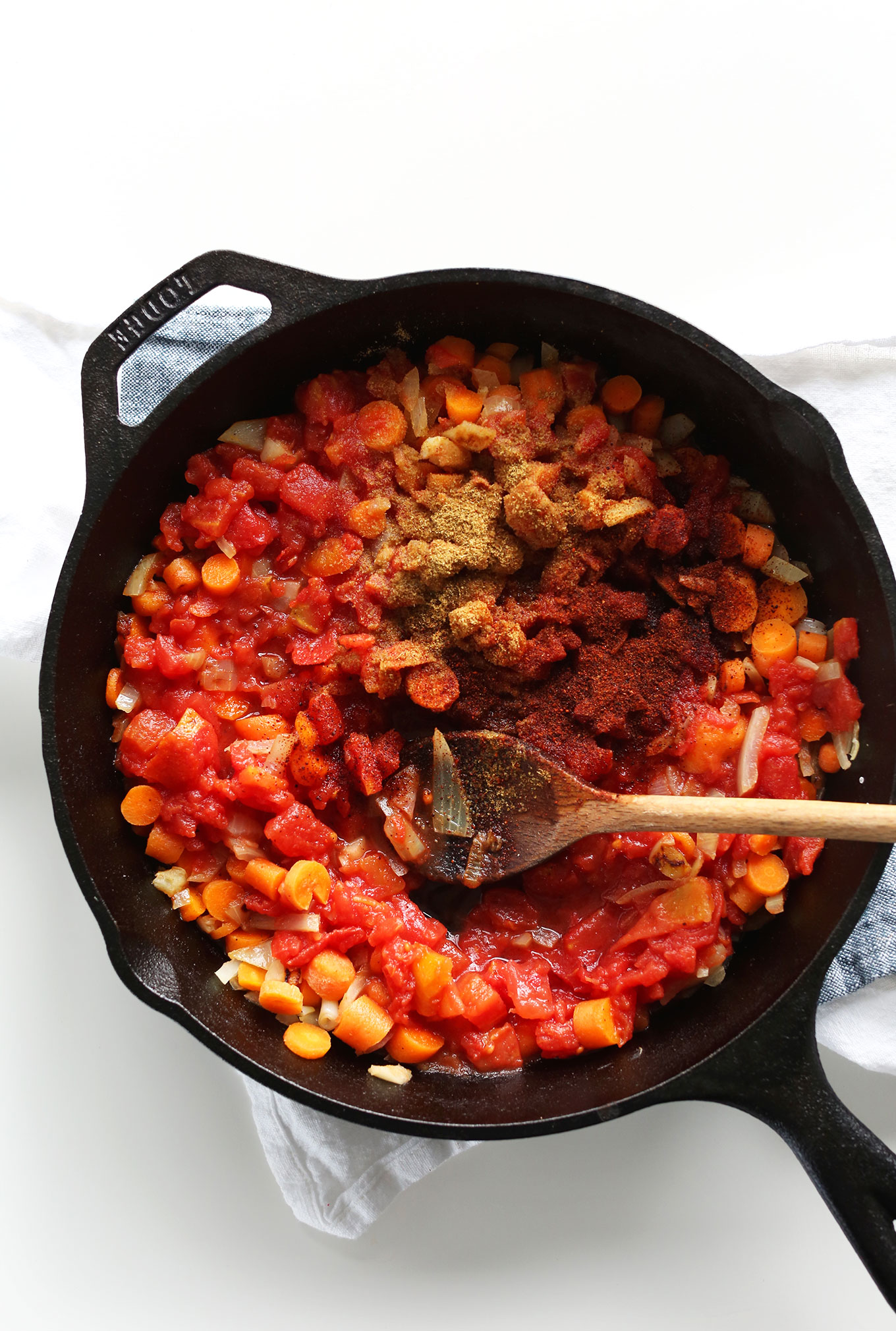 Cast iron skillet with ingredients for making homemade Chipotle Blended Red Salsa
