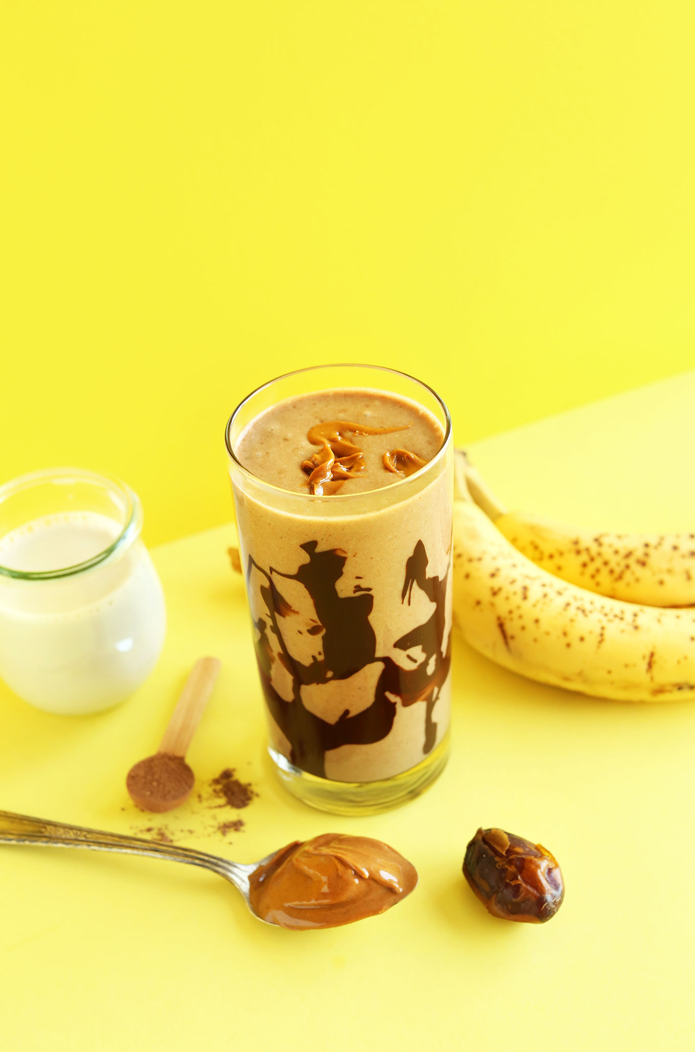 Creamy vegan Peanut Butter Chocolate Shake surrounded by ingredients used to make it