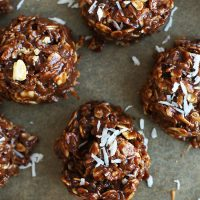 Parchment-lined baking sheet of No Bake Cookies topped with shredded coconut