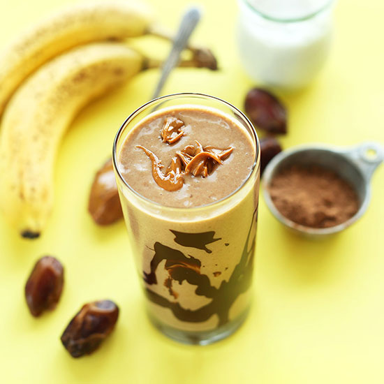 Tall glass of our PB Banana Shake surrounded by ingredients to make it
