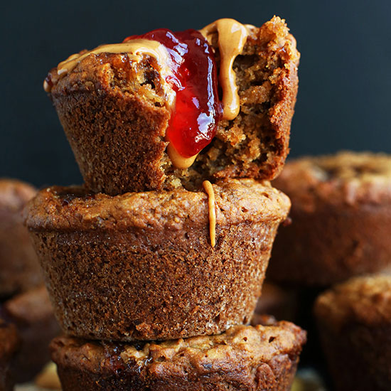 Stack of Vegan PB&J Muffins with the top one having a bite removed and jam and peanut butter dripping down it