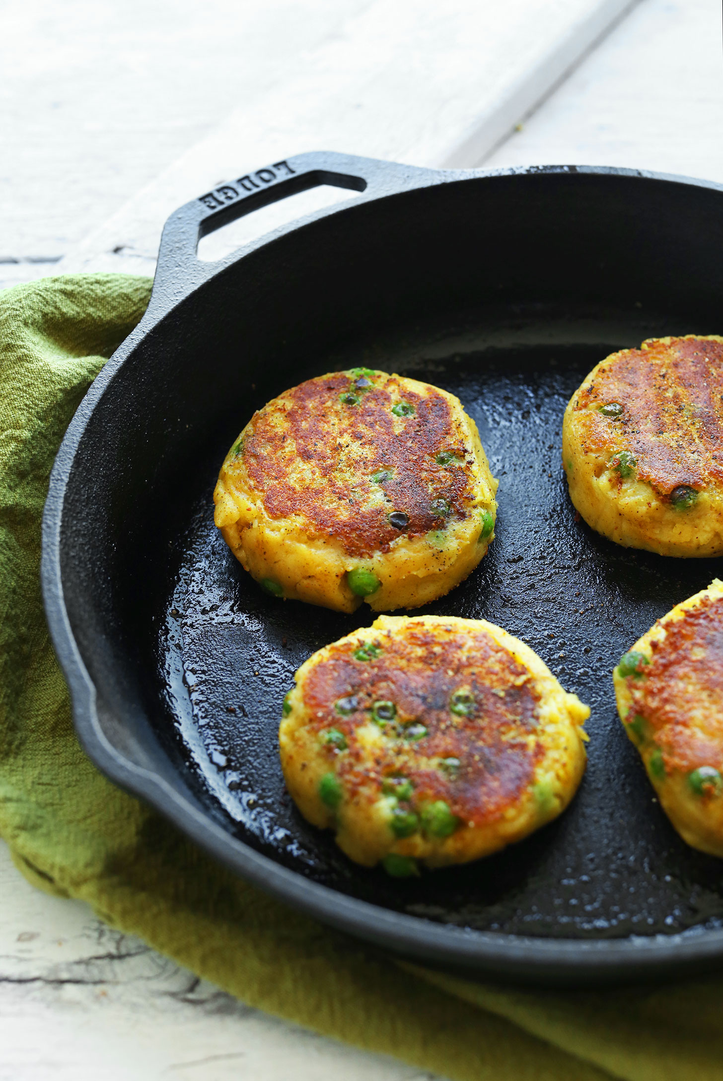 Cooking gluten-free vegan Samosa Potato Cakes in a cast-iron skillet