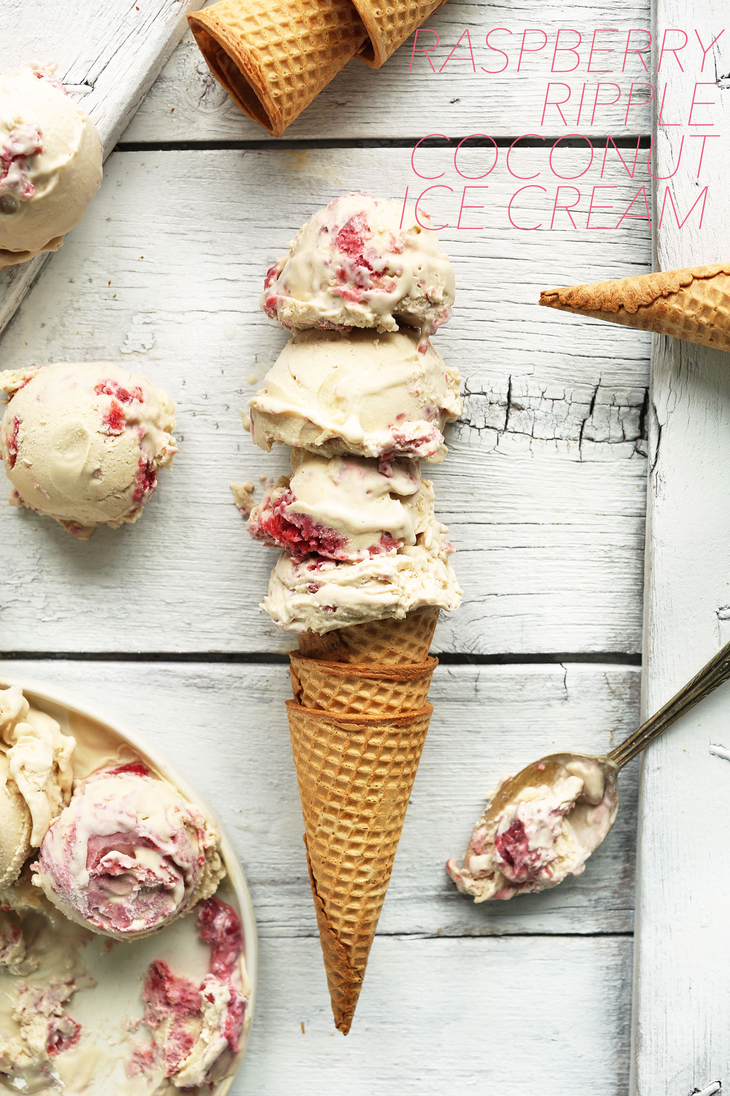 Scoops of homemade Raspberry Coconut Ice Cream piled high on a sugar cone
