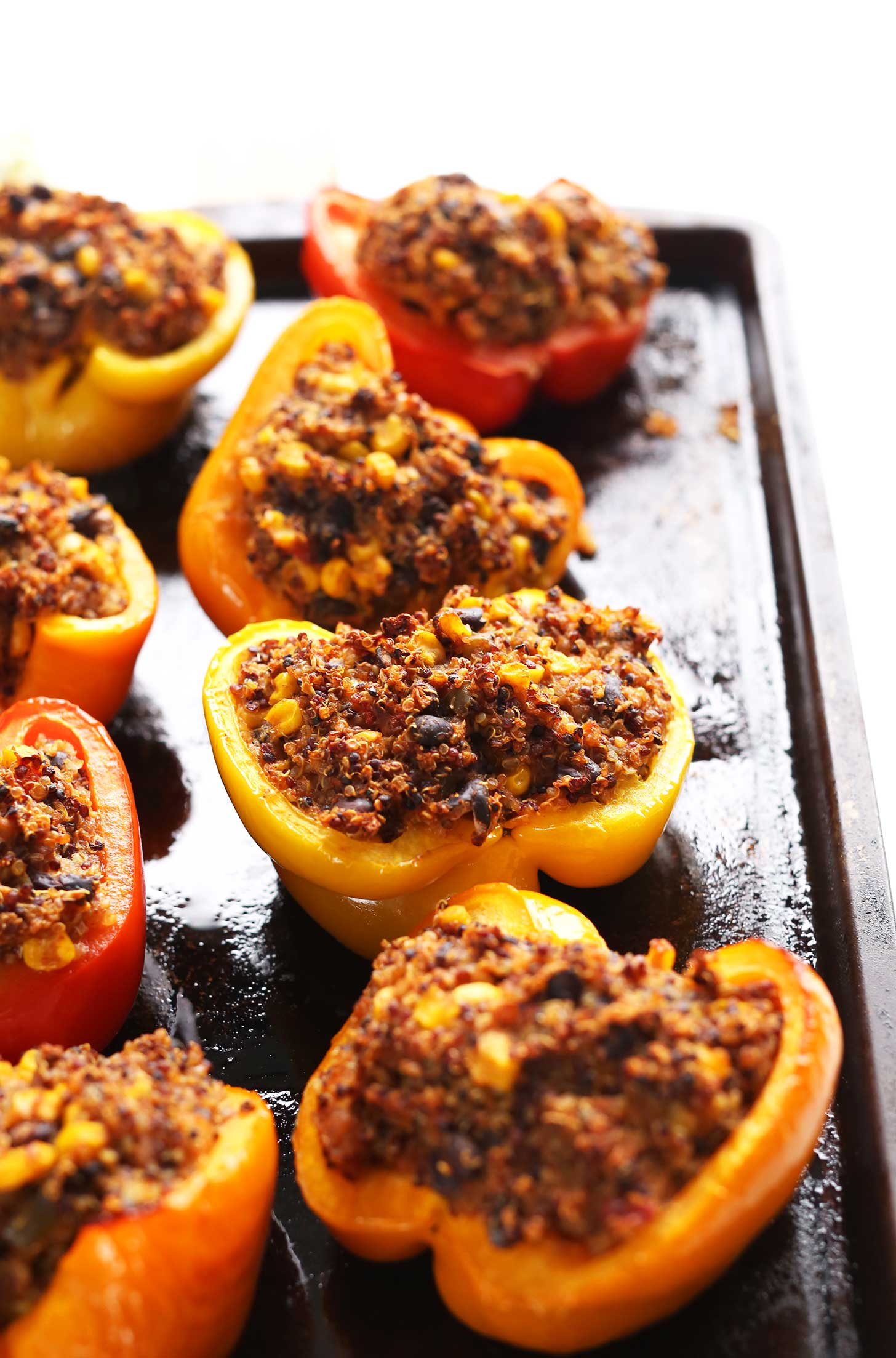 Baking sheet filled with protein-rich vegan Spanish Quinoa Stuffed Peppers