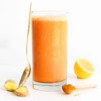 Gold spoon leaning against a glass of our Carrot Ginger Turmeric Smoothie recipe