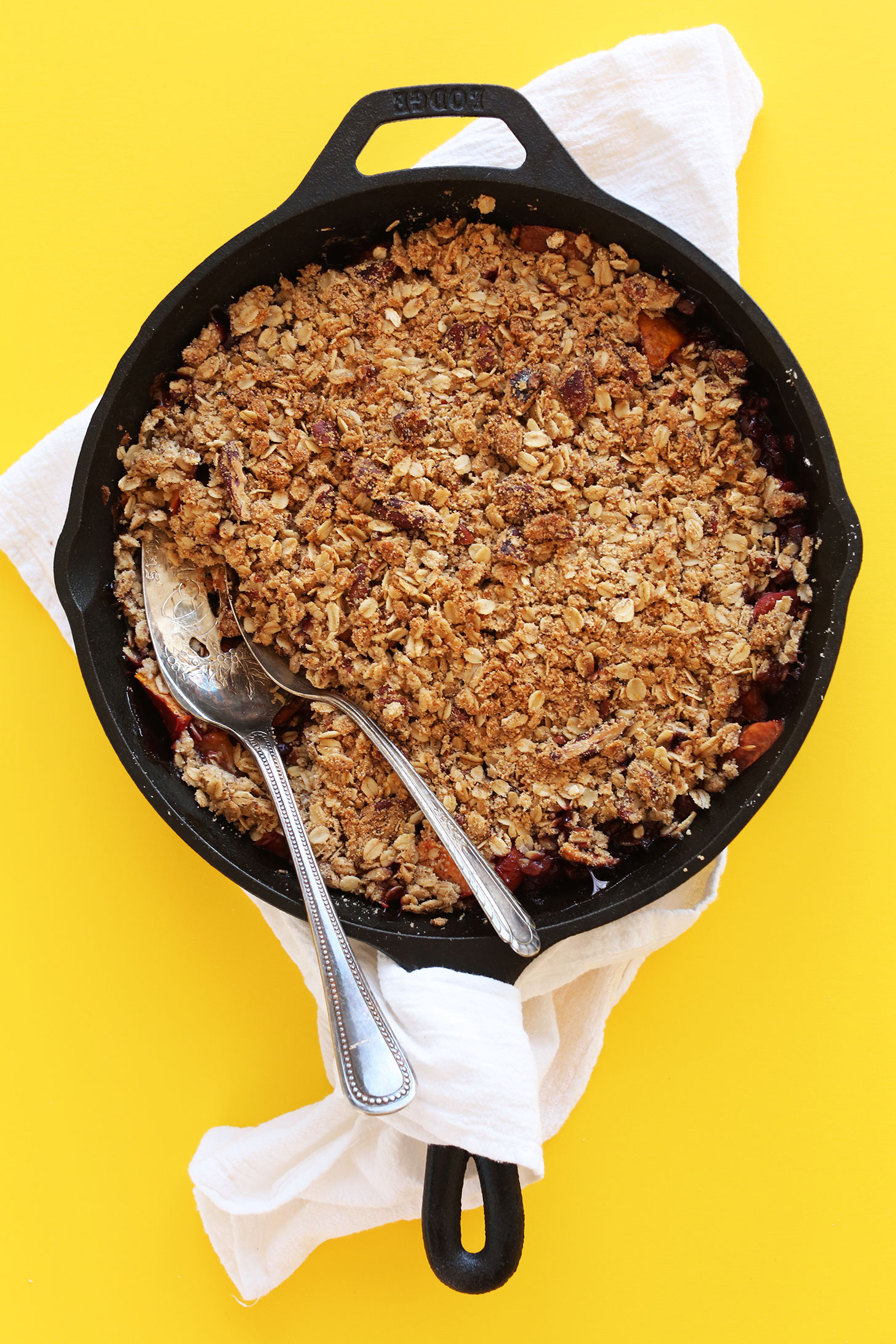 Cast-iron skillet filled with gluten-free vegan summer Peach Crisp