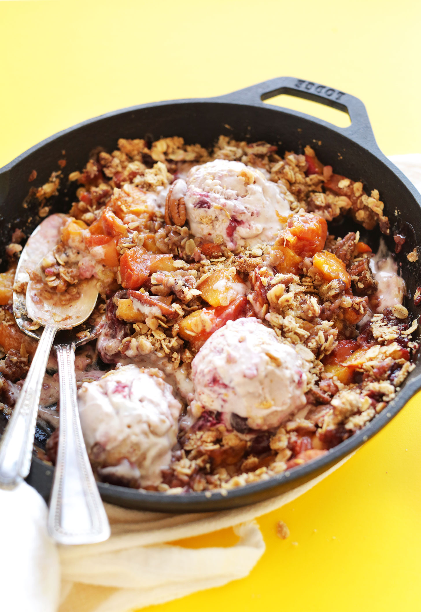 Spoons in a cast-iron skillet for eating our Summer Peach Crisp with dairy-free ice cream
