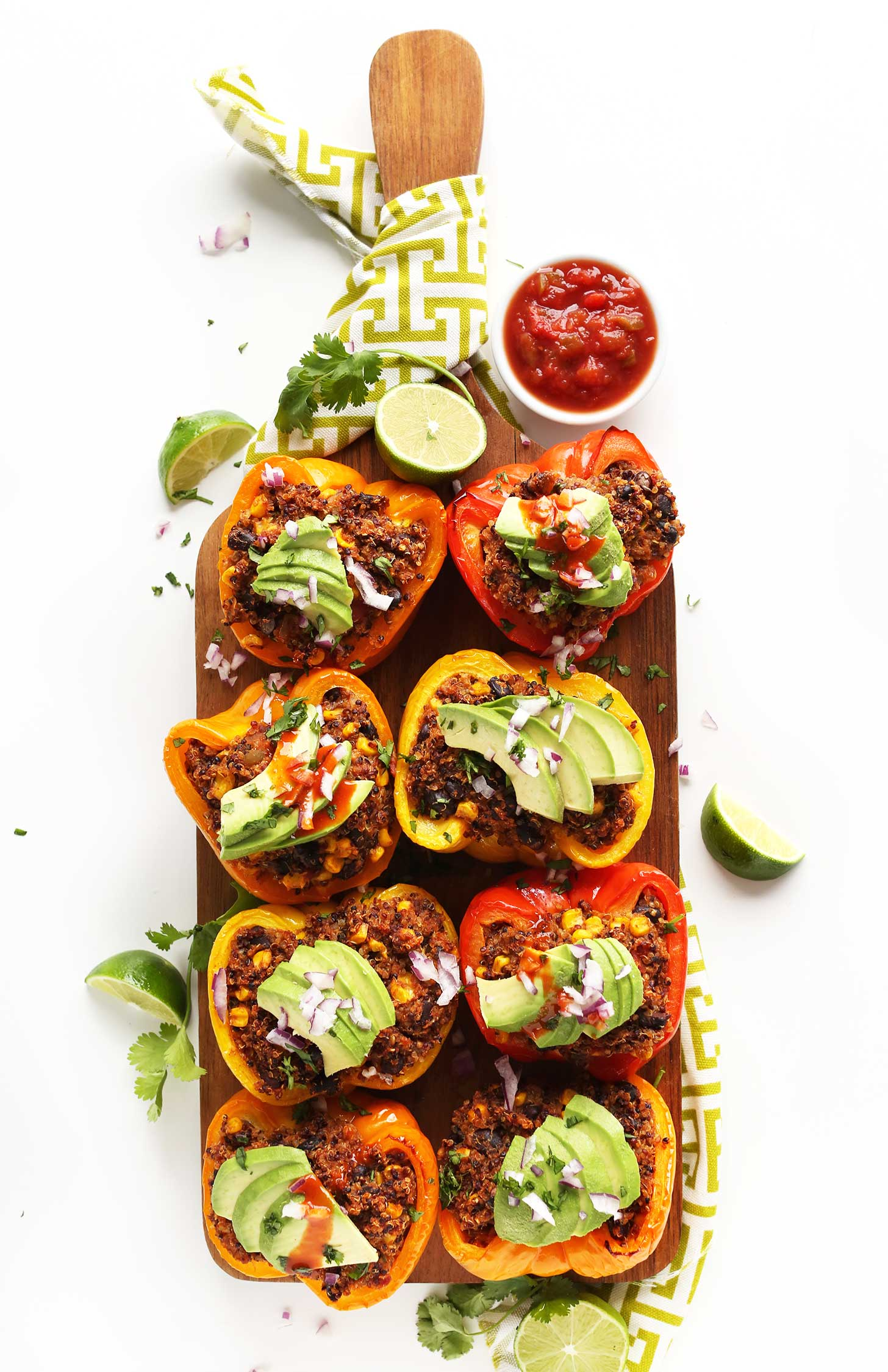 Wood platter filled with gluten-free vegan Spanish Quinoa Stuffed Peppers