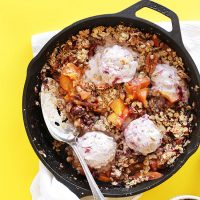 Cast-iron skillet filled with our Easy Peach Crisp recipe topped with scoops of ice cream