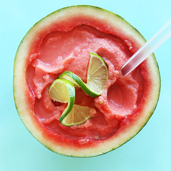 Homemade Watermelon Slushie served in a watermelon rind with fresh limes on top