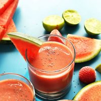 Two short glasses of our Strawberry Watermelon Smoothie recipe beside ingredients used to make it