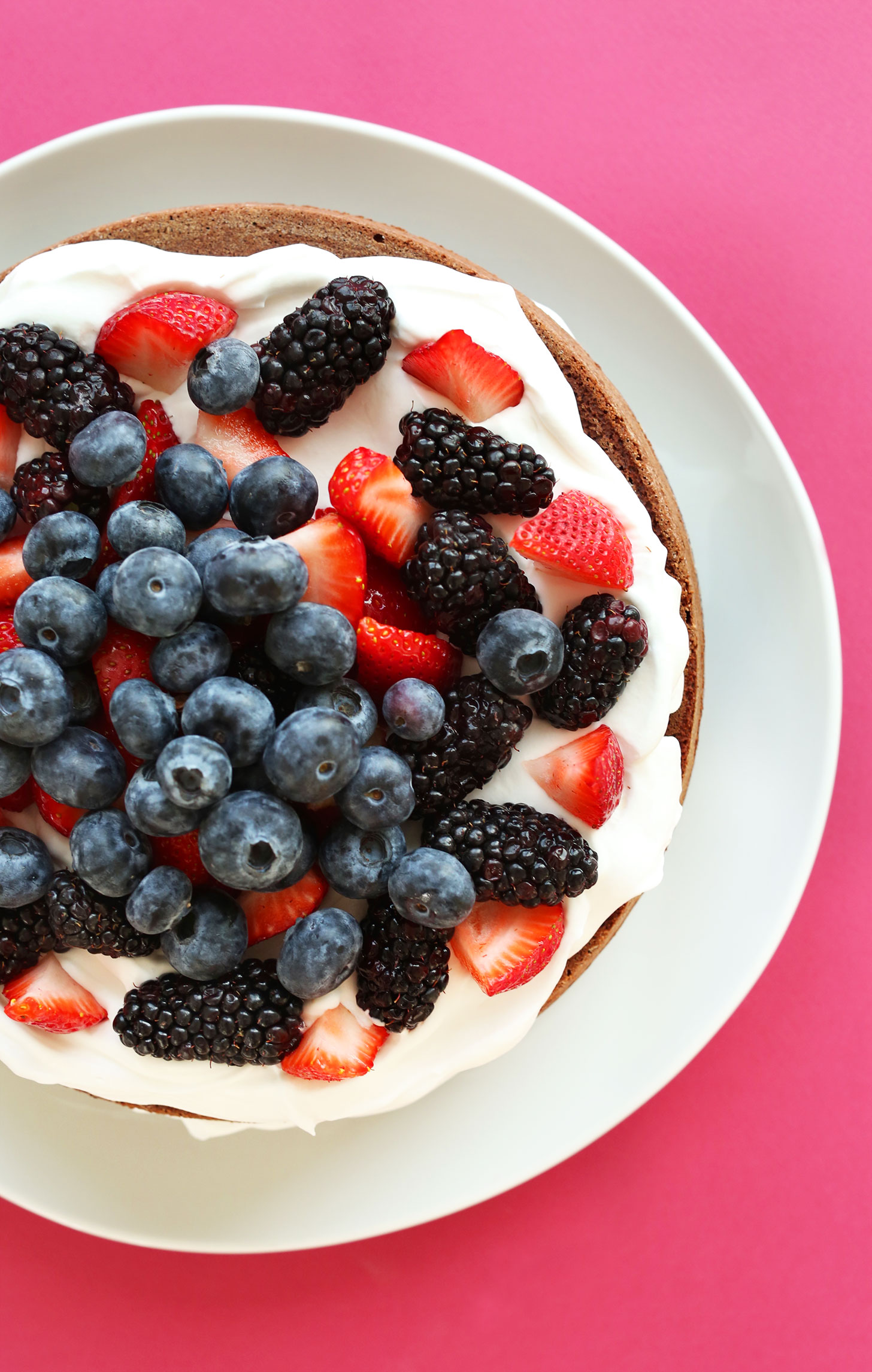 Plate of gluten-free vegan Chocolate Cake with Coconut Whip and Berries