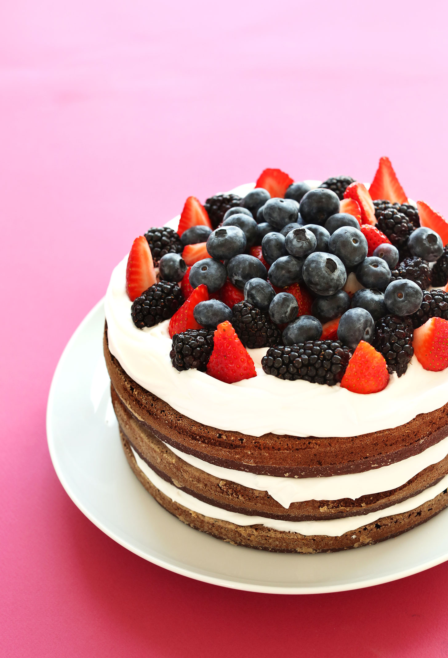 Three layer gluten-free vegan Chocolate Cake with Coconut Whipped Cream topped with fresh berries