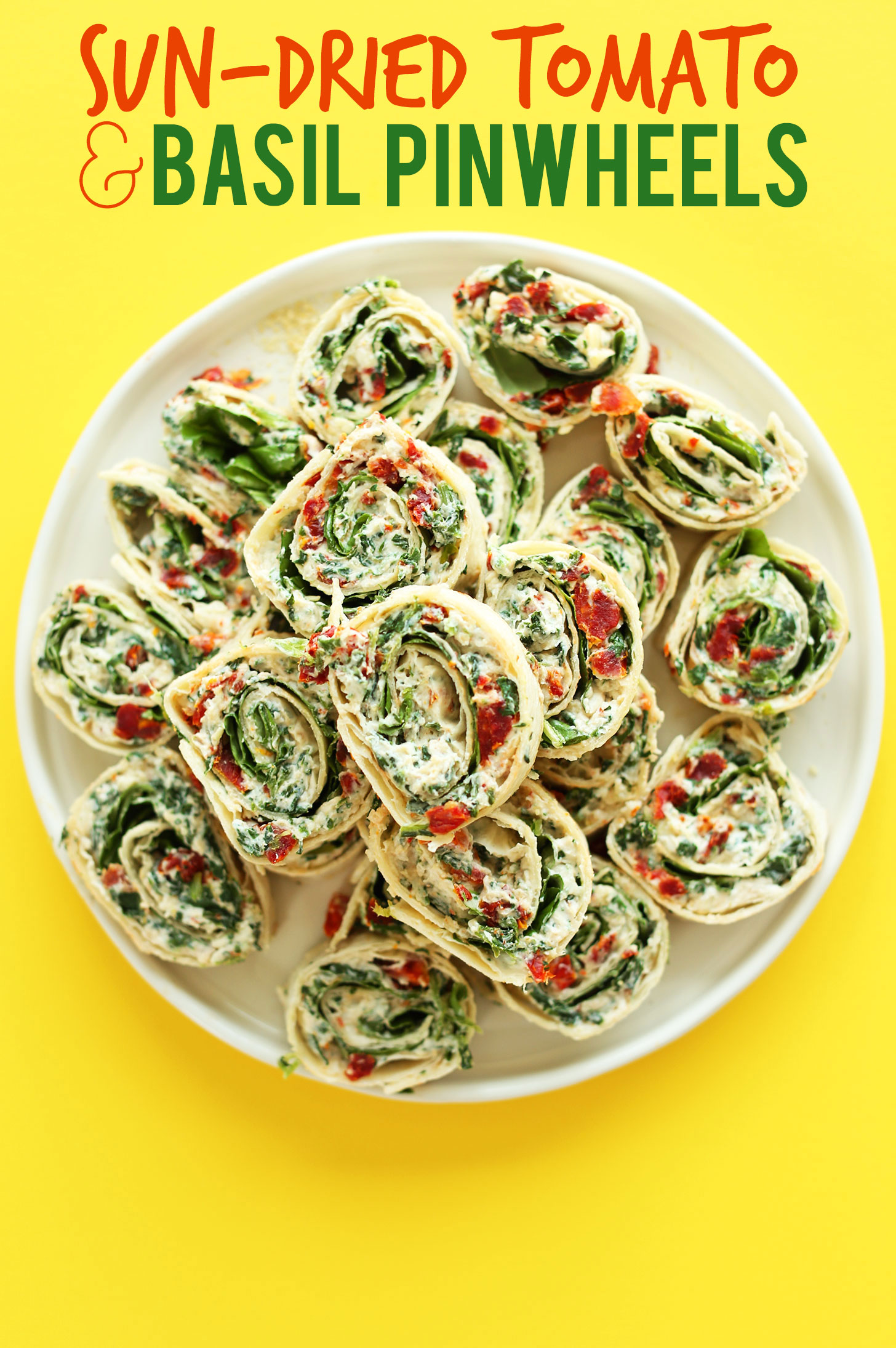 Sun-Dried Tomato and Basil Pinwheels stacked on a plate for a vegan party appetizer