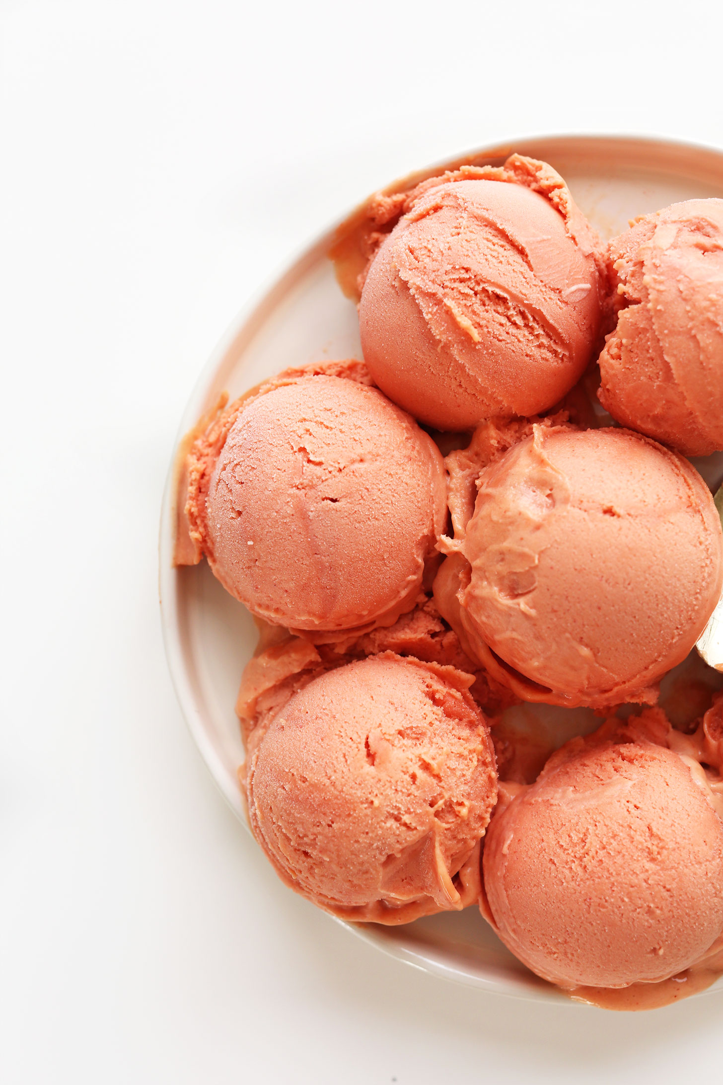 Scoops of Mango Raspberry Coconut Sorbet for a refreshing vegan summer dessert