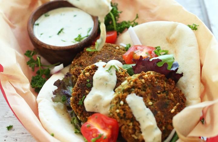 Drizzling dressing onto healthy vegan falafel