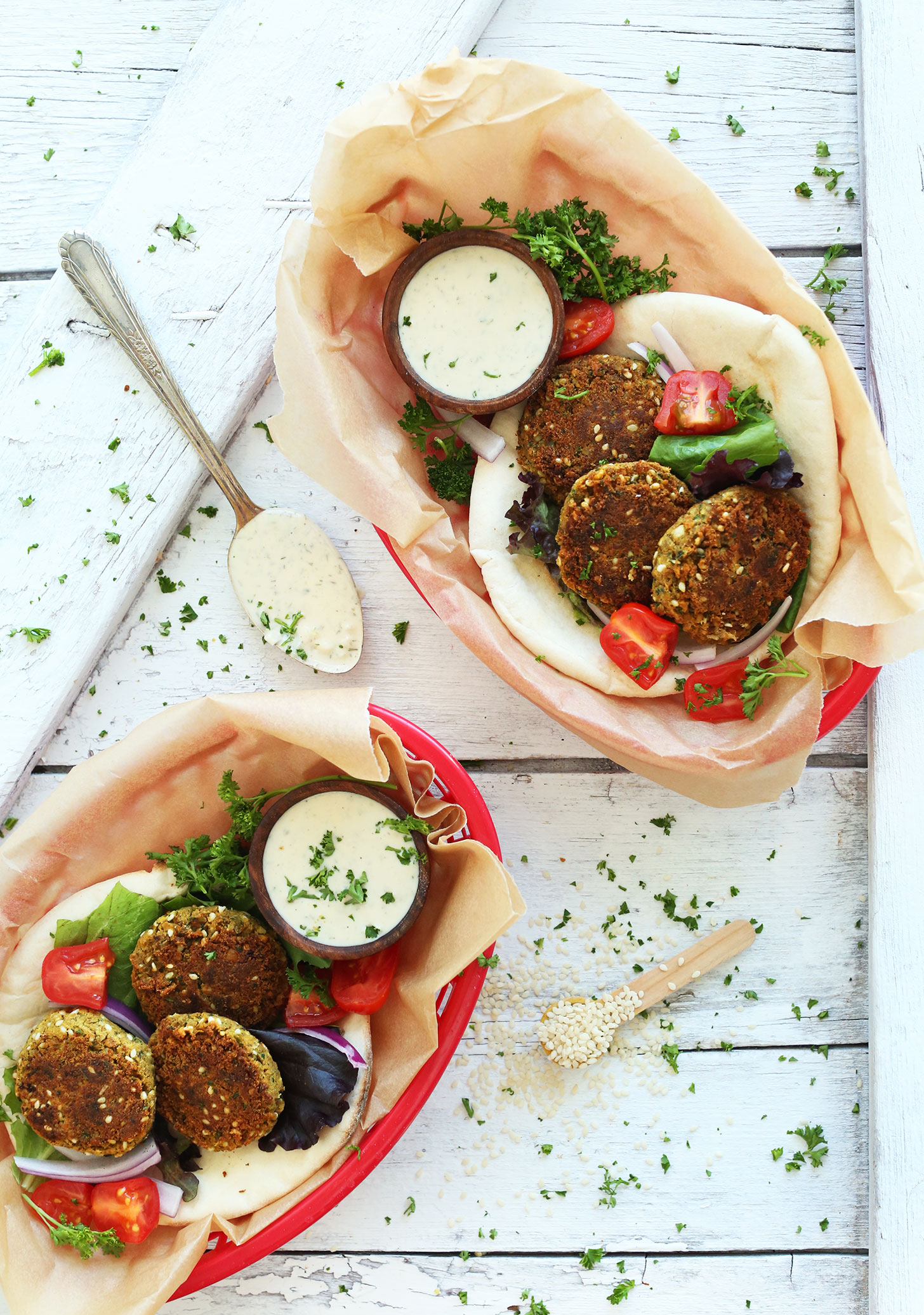 Serving containers filled with pita bread topped with homemade Simple Vegan Falafel