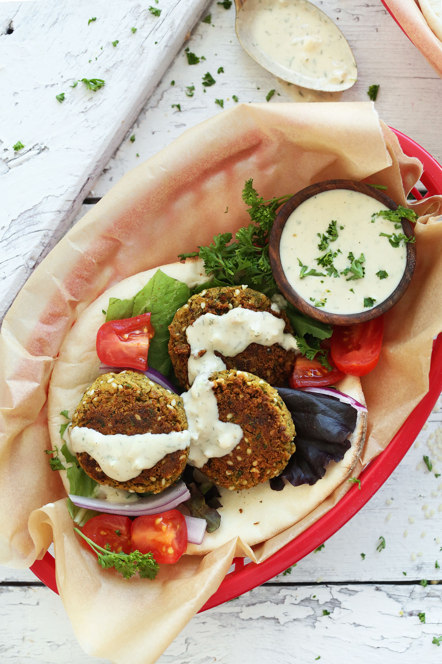 Basket filled with Vegan Falafel on pita bread with 4-ingredient dressing and fresh vegetables