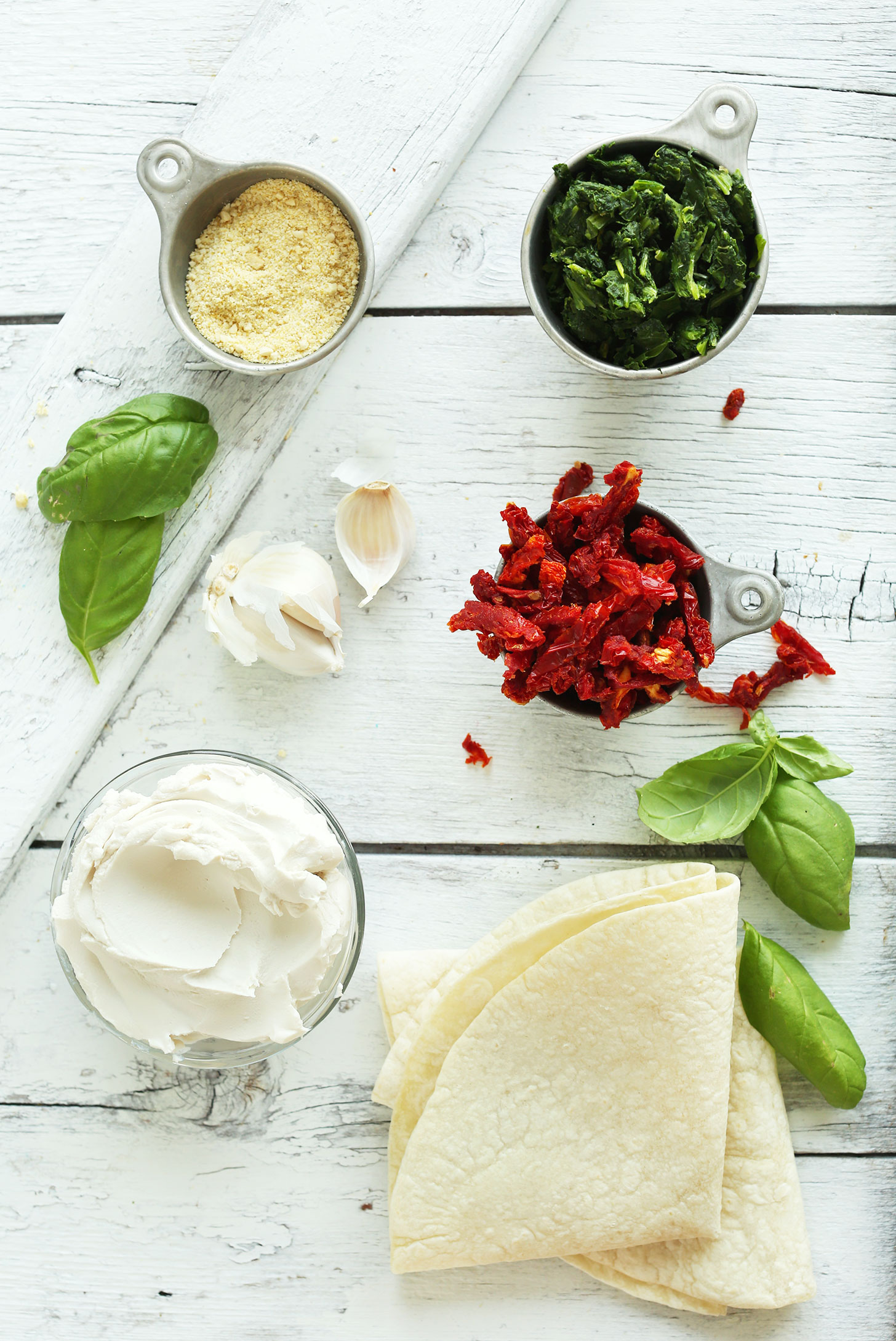 Vegan parmesan cheese, frozen spinach, sun-dried tomatoes, basil, tortillas, garlic, and vegan cream cheese for making a vegan appetizer