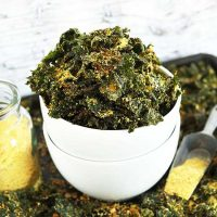 Bowl of Cheesy Kale Chips on a baking sheet with more chips and nutritional yeast