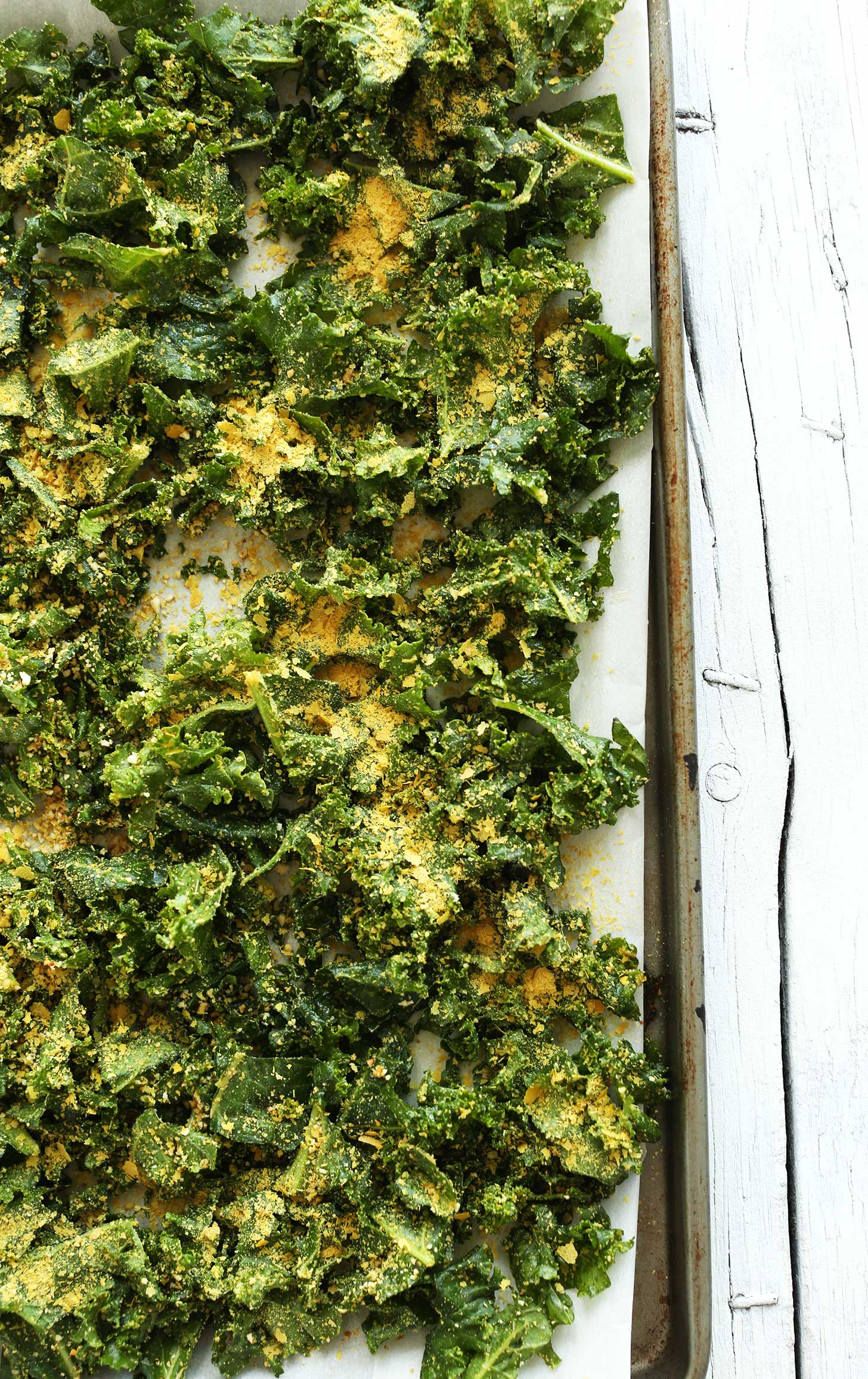 Parchment-lined baking sheet with kale, nutritional yeast, and spices for making homemade kale chips