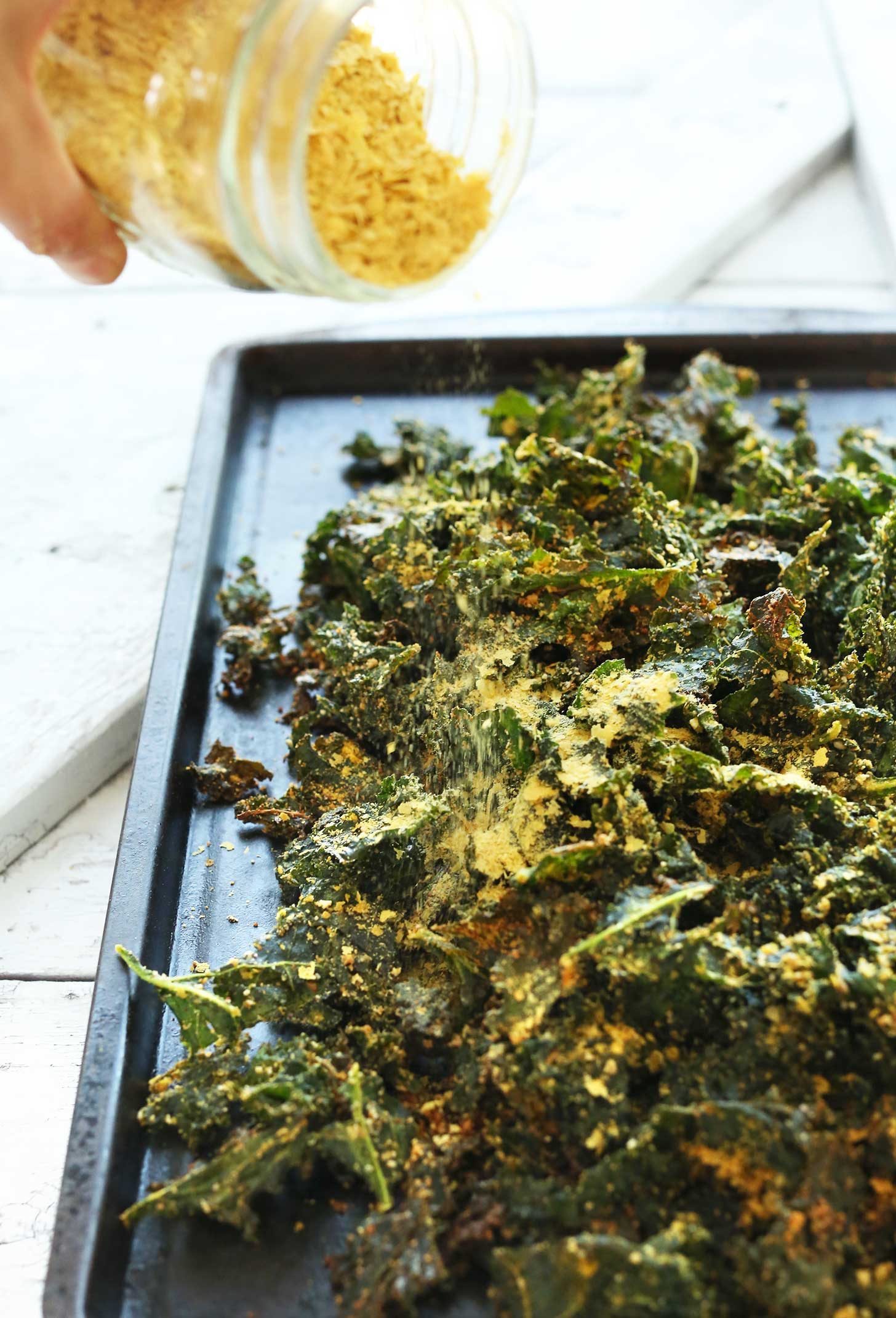 Sprinkling nutritional yeast onto kale chips for a delicious vegan snack recipe