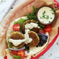 Takeout basket filled with Easy Vegan Falafel on pita with vegetables and sauce