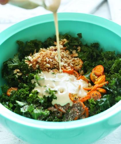 Pouring tahini dressing onto a satisfying vegan kale salad recipe