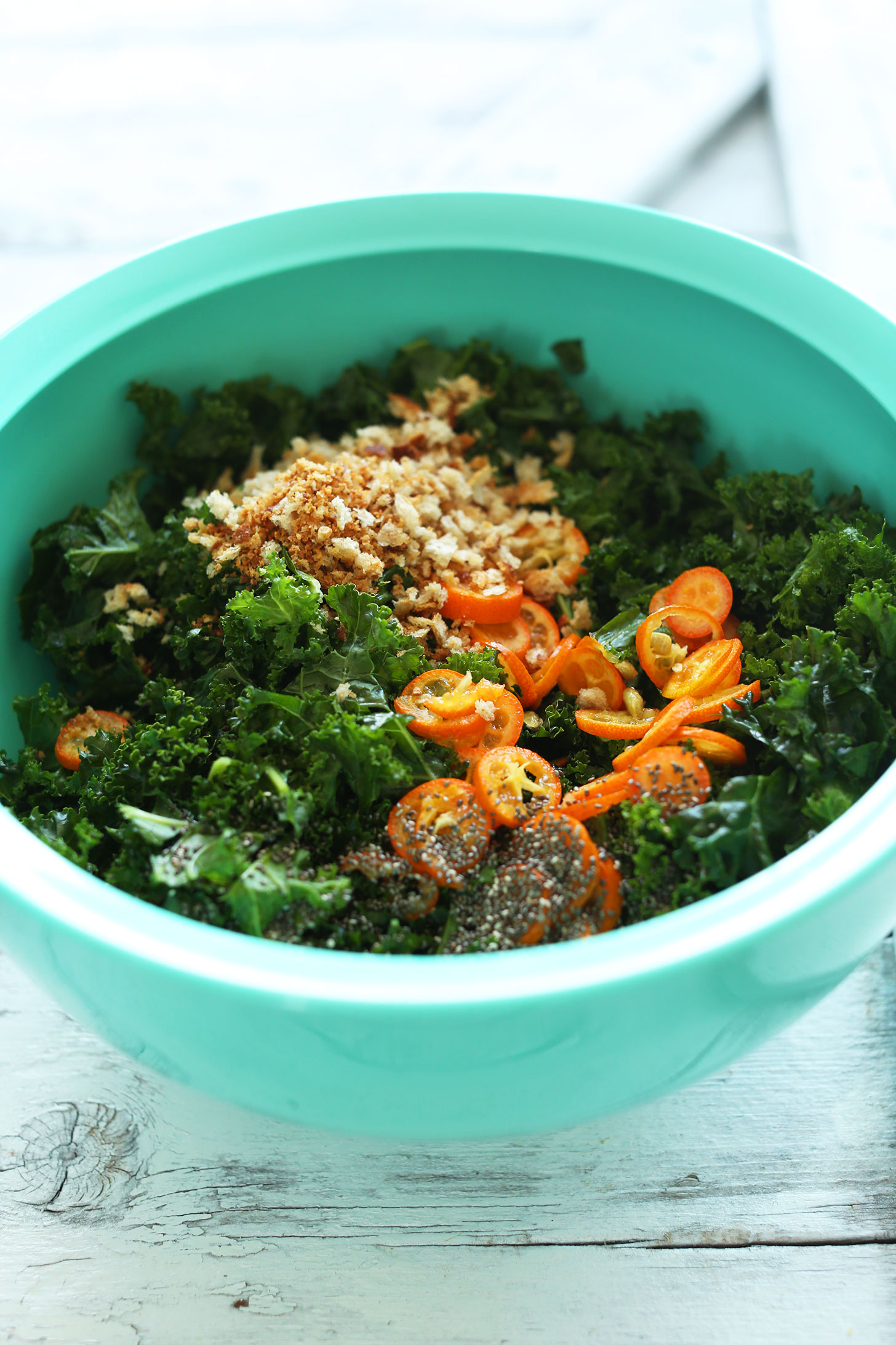 Big bowl of vegan Kale Salad with Kumquats, Chia Seeds, and Breadcrumbs