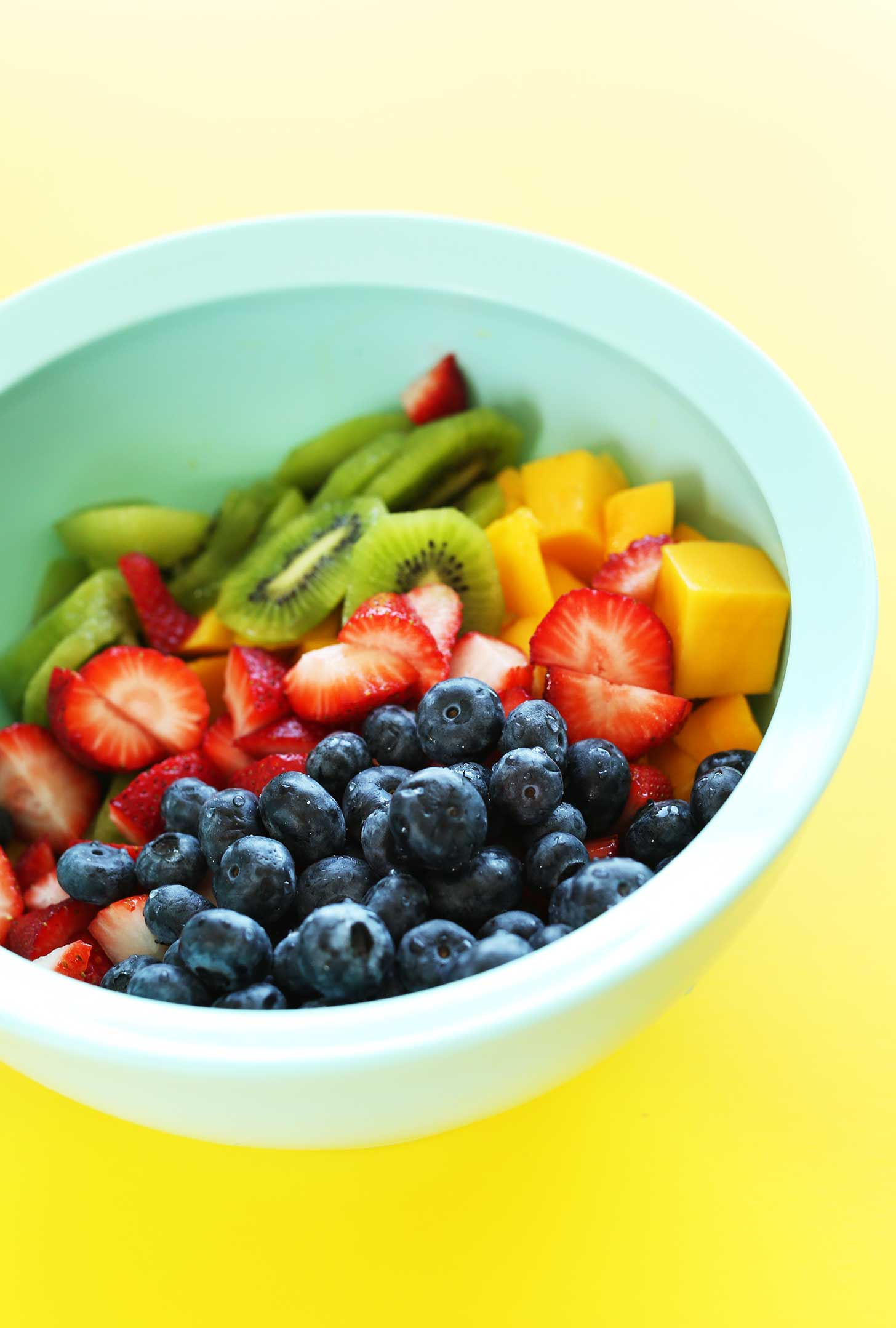 Bowl of mango, strawberries, kiwi, and blueberries for an incredible summer side dish