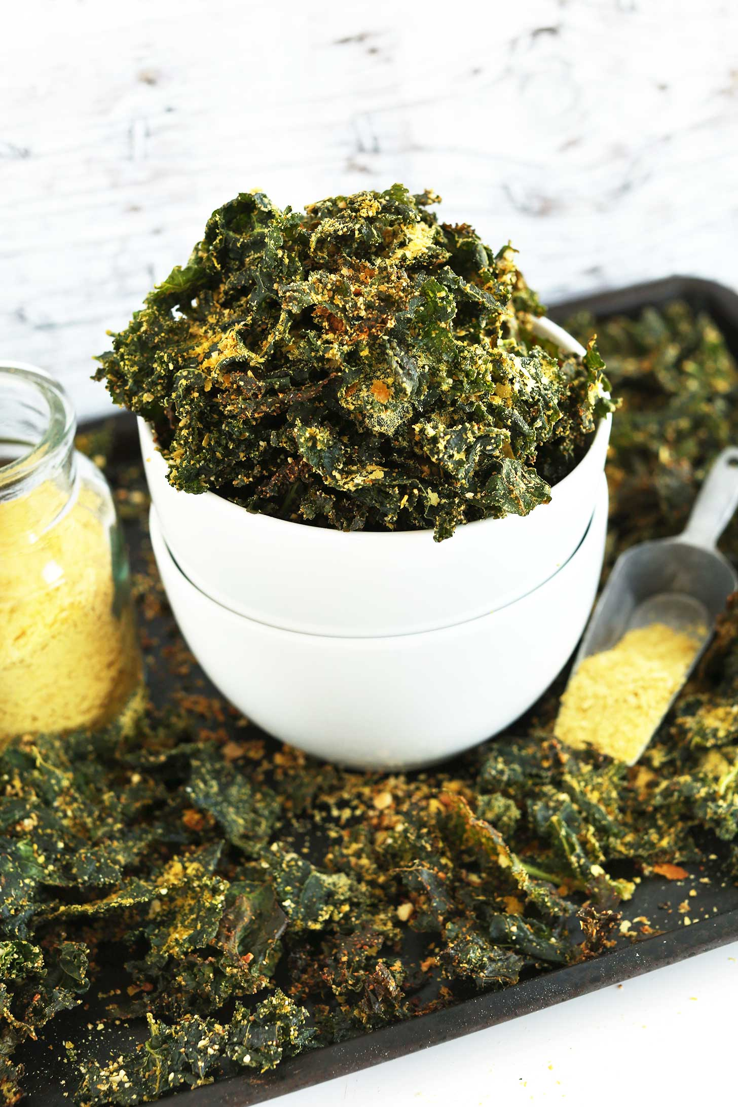 Bowl of our easy to make Cheesy Vegan Kale Chips on a baking sheet