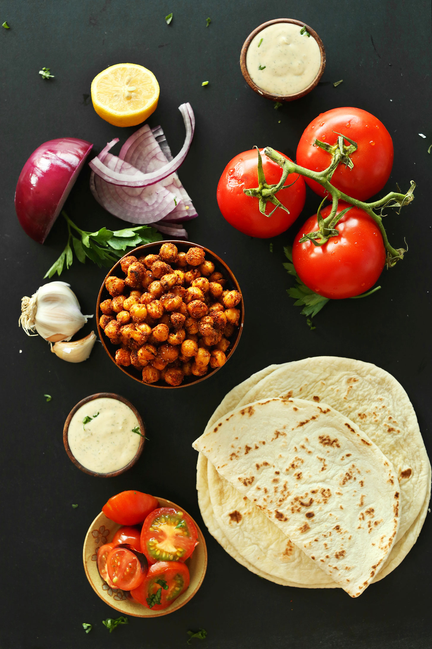 Tomatoes, Shawarma-Spiced Chickpeas, red onion, flatbread, and garlic dill sauce for making Healthy Vegan Wraps