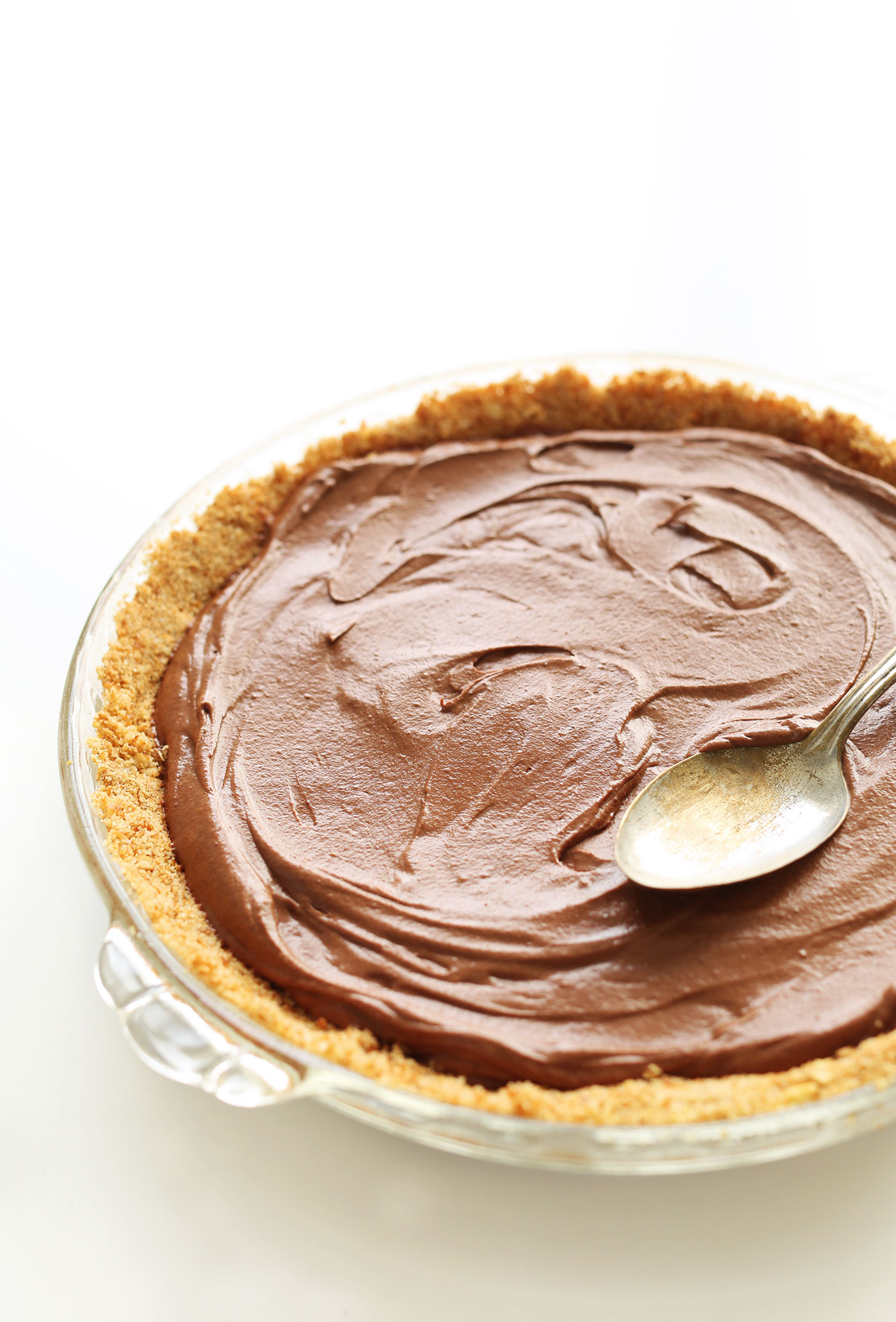 Using the back of a spoon to even out the chocolate filling of our vegan pie