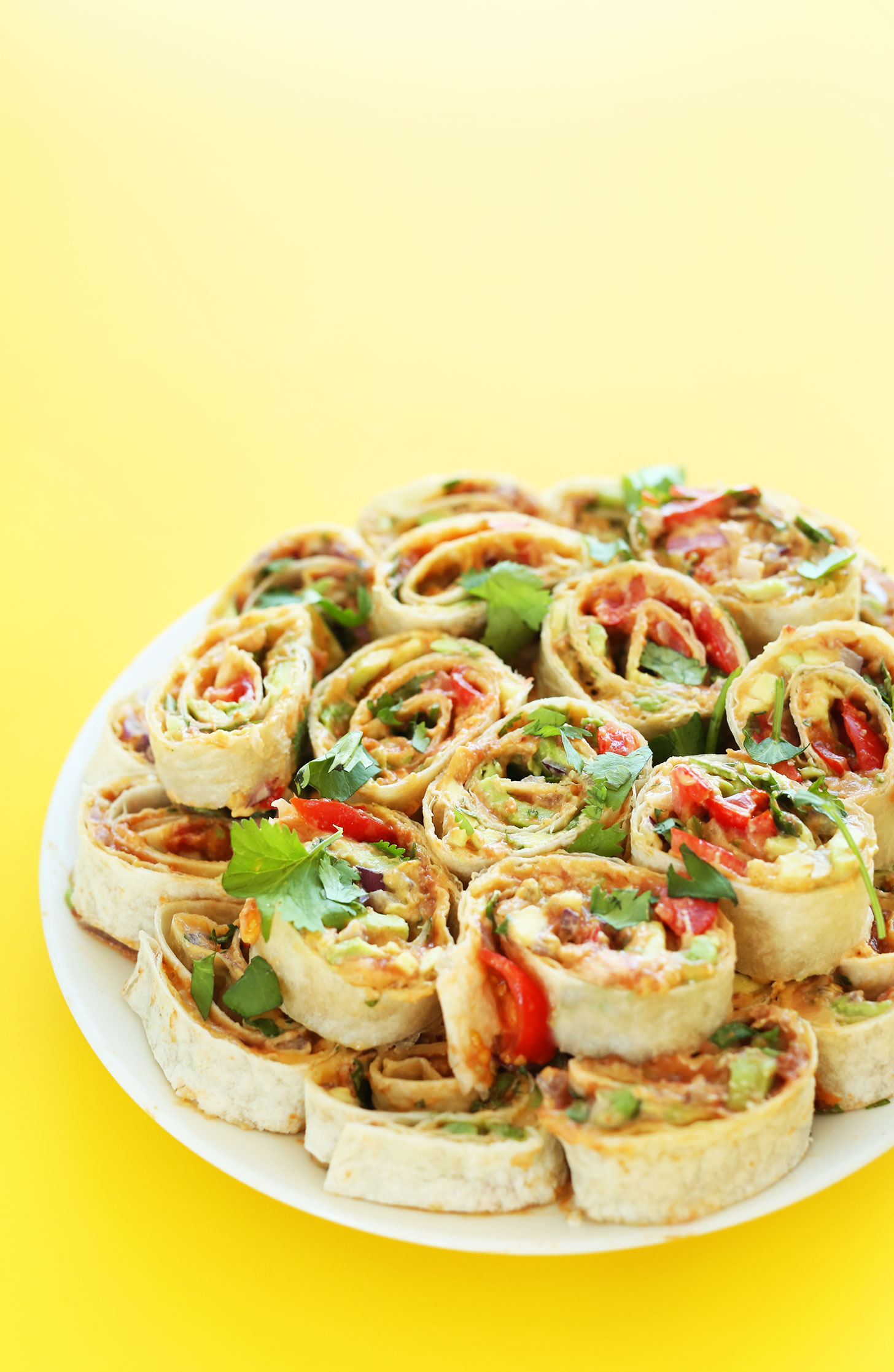 Plate filled with our Mexican Pinwheels recipe with refried beans, avocado, onion, cilantro, and tomato