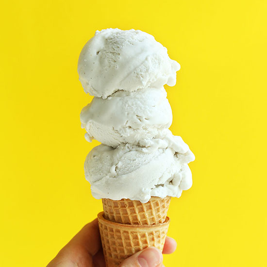 Triple scooped Vanilla Bean Coconut Ice Cream on a stack of sugar cones