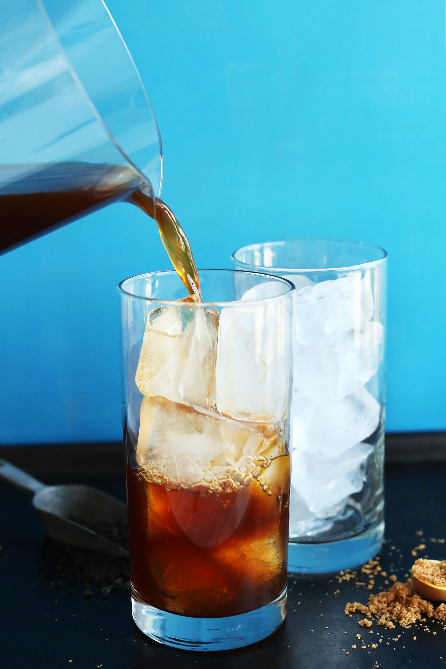 Pouring tea over ice cubes for Easy Vegan Coconut Thai Iced Tea