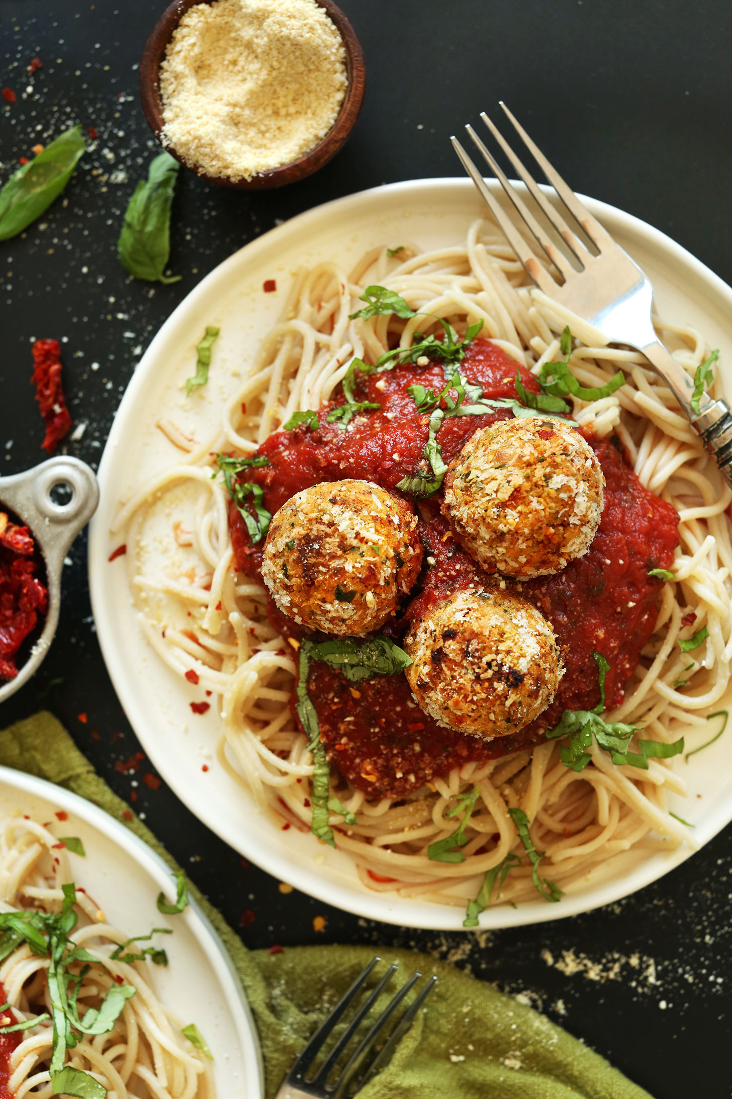 Dinner plate of healthy Chickpea Meatballs atop spaghetti for a plant-based meal