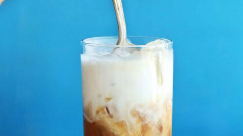 Stirring Thai Iced Tea for a refreshing vegan summer beverage