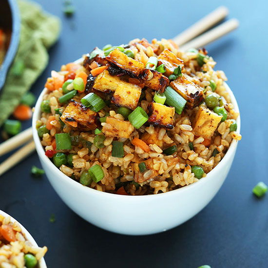 Chopsticks beside a bowl of Vegan Fried Rice topped with tofu