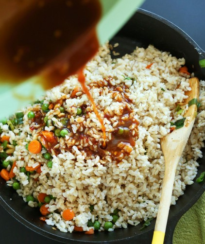 Pouring sauce onto a batch of our Healthy Vegan Fried Rice